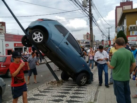 Carro fica pendurado em poste em Curitiba, no Paraná (Foto João Zacarias Zubek/G1).