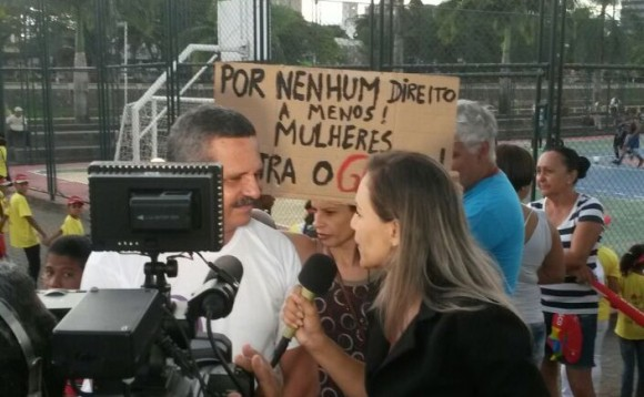 "Prefeito Vane concede entrevista, enquanto ativista exibe cartaz contra o ""golpe"" (Foto Pimenta)."