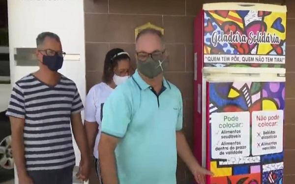 CASAL INSTALA GELADEIRA COM ALIMENTOS NA PORTA DE CASA PARA PESSOAS CARENTES